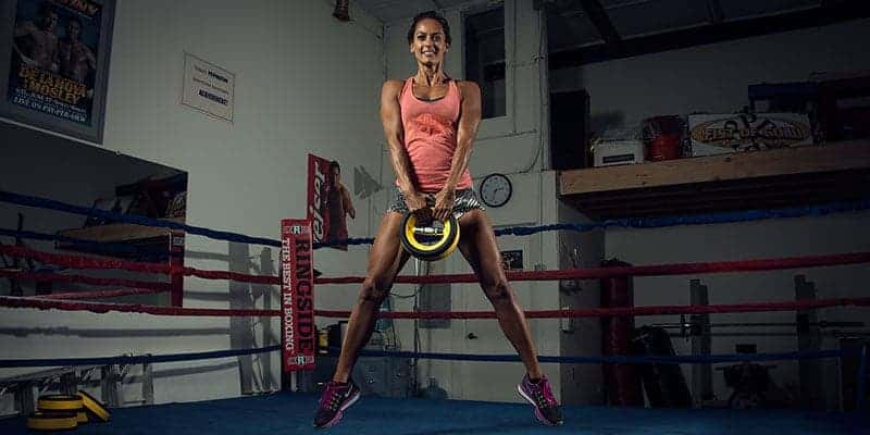 Christel jumping holding a dumbbell