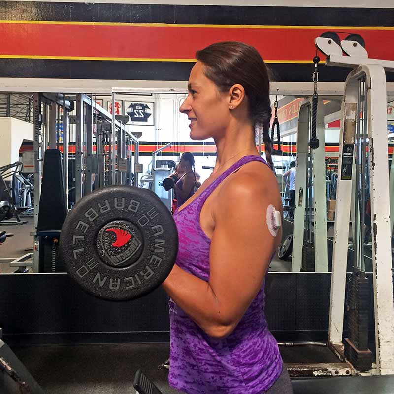 Christel doing biceps curls in the gym with a dexcom CGM on her upper arm.
