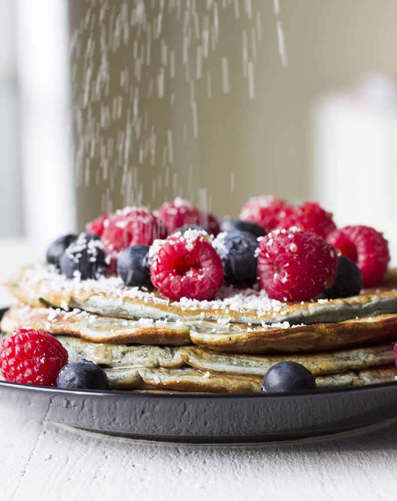 Sprinkling stevia over a stack of pancakes with berries and sugar free syrup on top