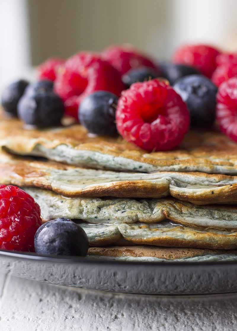 A stack of Protein Pancakes on a black plate with mixed berries on top.