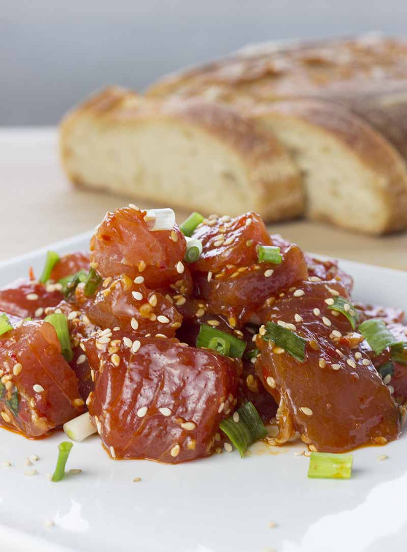 Freshly made ahi tuna poke on a plate with bread