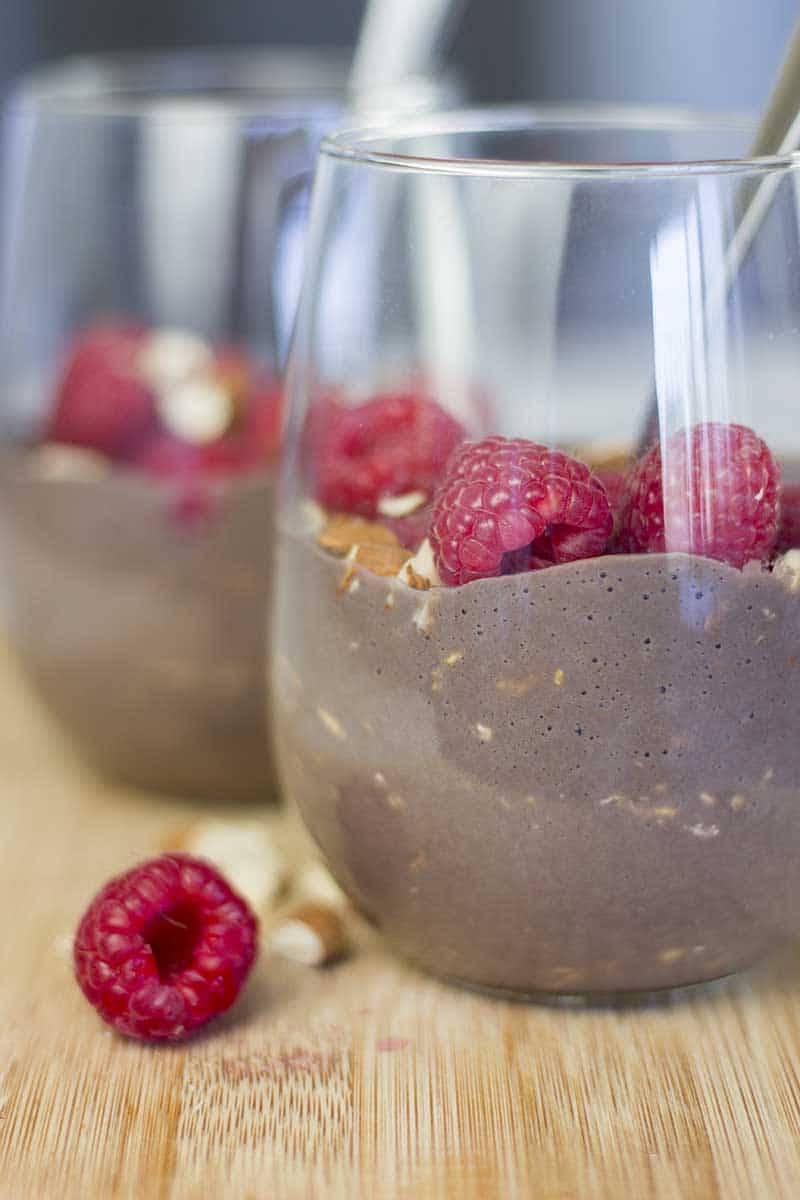High Protein Chocolate Overnight Oats with Almond Milk in a glass with raspberries and almonds on top