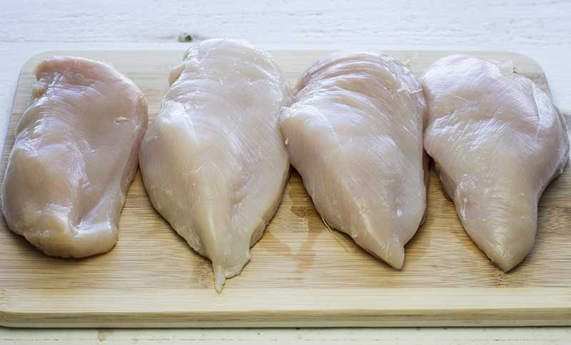 Four cleaned chicken breasts on a cutting board