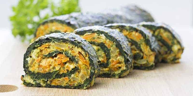 4 pieces of spinach roll on a wooden cutting board