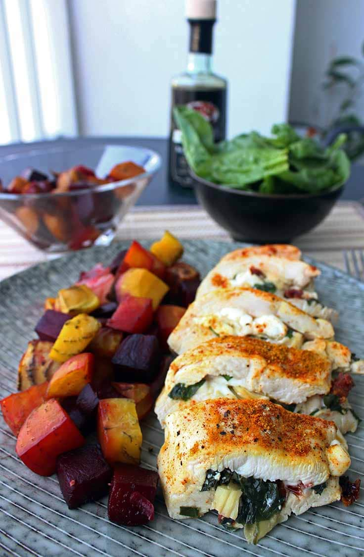Stuffed chicken breast, sliced and plated with a side of root vegetables.