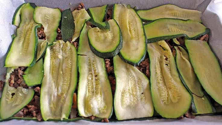 Alternating layers of zucchini and beef in the baking tray