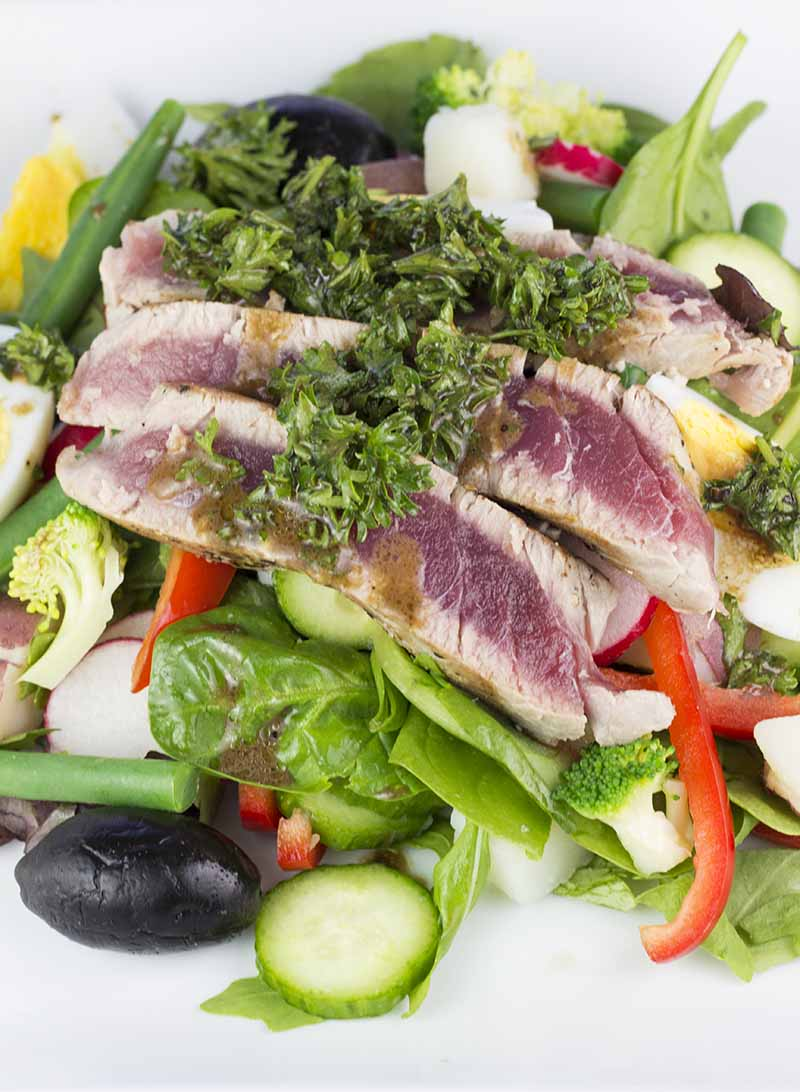 Seared tuna over salad and topped with parsley mustard dressing, as seen from above