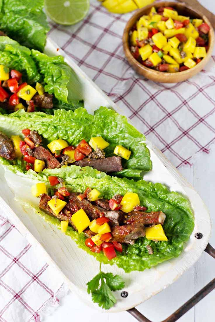 Beef Lettuce Wraps with Mango Salsa on a wood serving plate