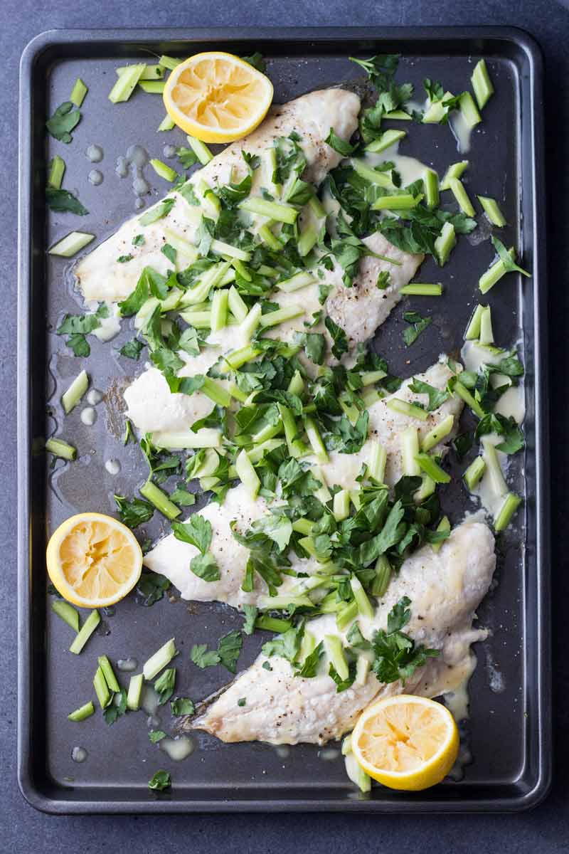 Snapper with lemon halves and celery and parsley salad on a baking tray, as seen from above