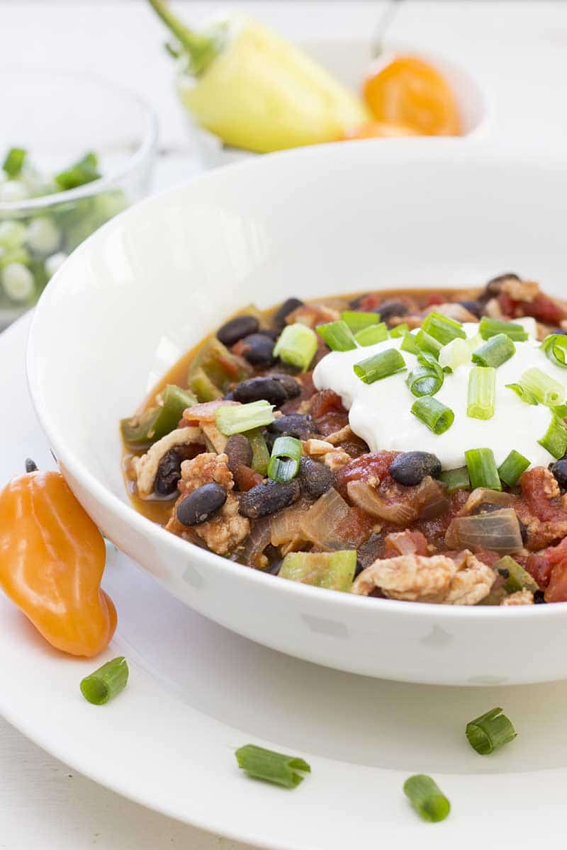 Simple turkey chili in a bowl, topped with sour cream and sliced green onions