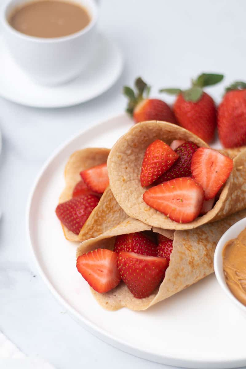 Low Carb Cottage Cheese Pancakes filled with sliced strawberries on a plate with a side of peanut butter in a ramekin