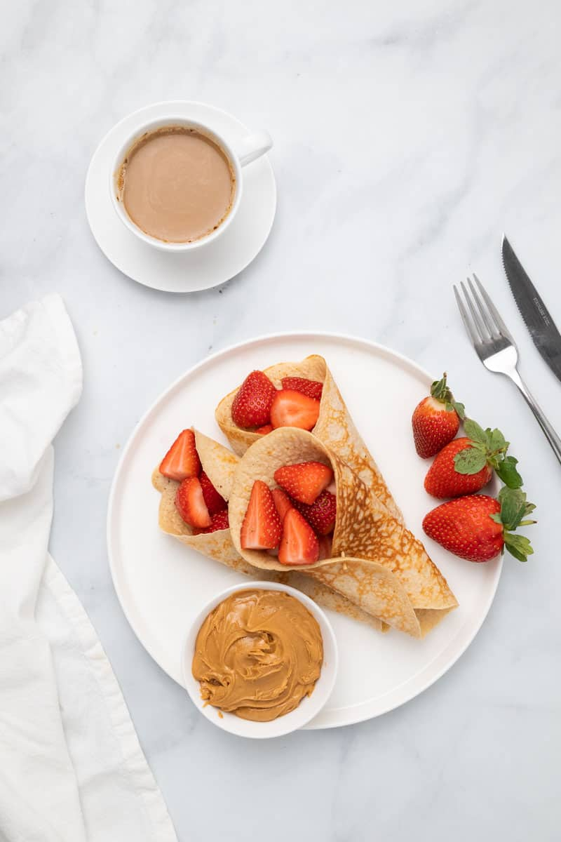 Plate with pancakes, strawberries, and peanut butter
