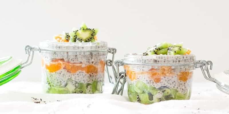 2 mason jars with coconut chia seed pudding, fruit, and shredded coconut.