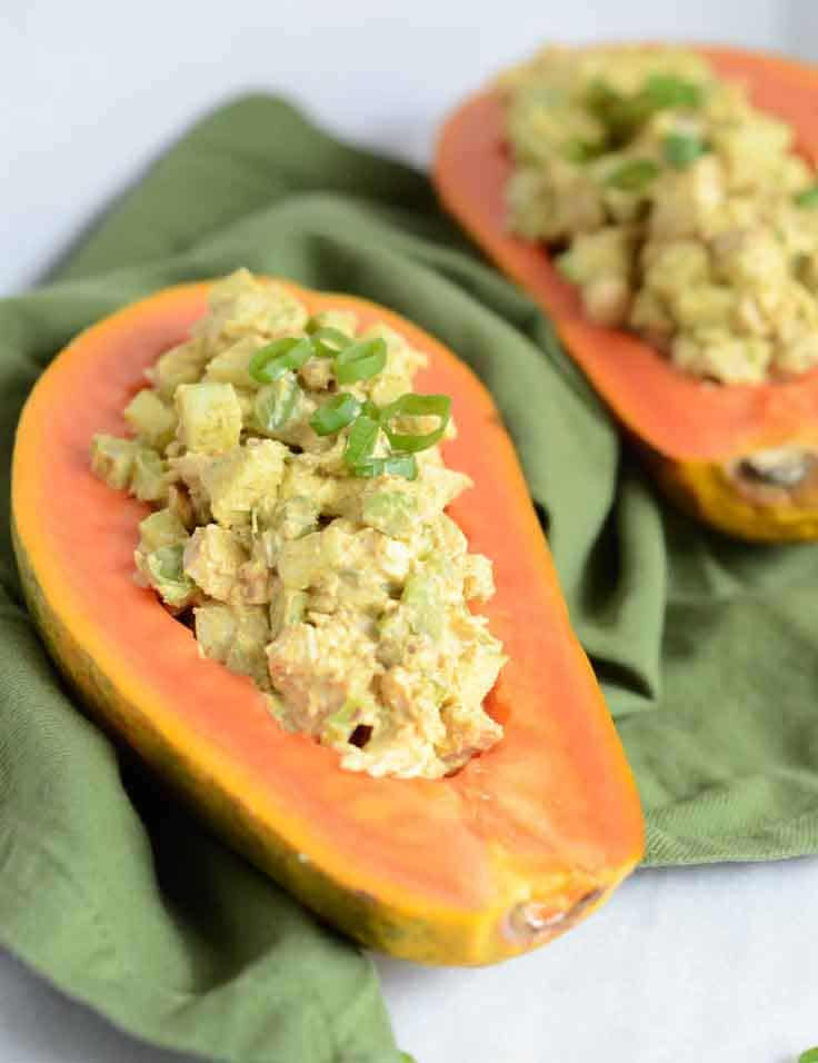 Chicken salad served in half of a scooped-out papaya with sliced green onions on top