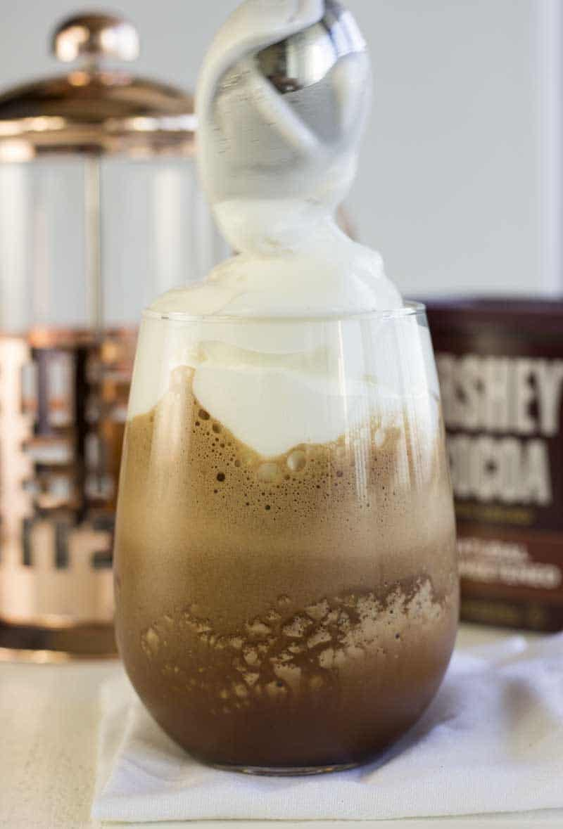 Iced Chocolate Coffee Protein Shake in a glass being topped with whipped egg whites