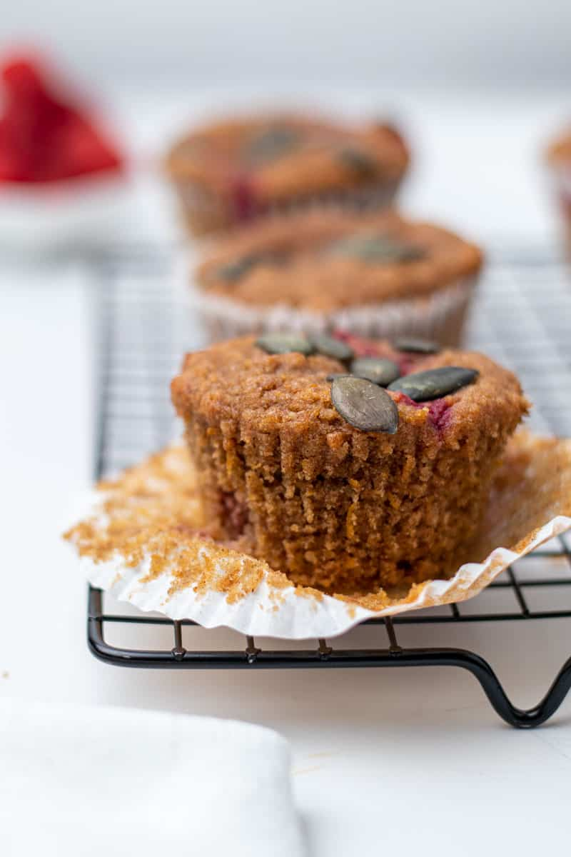 Three pumpkin raspberry muffins on a cooling rack
