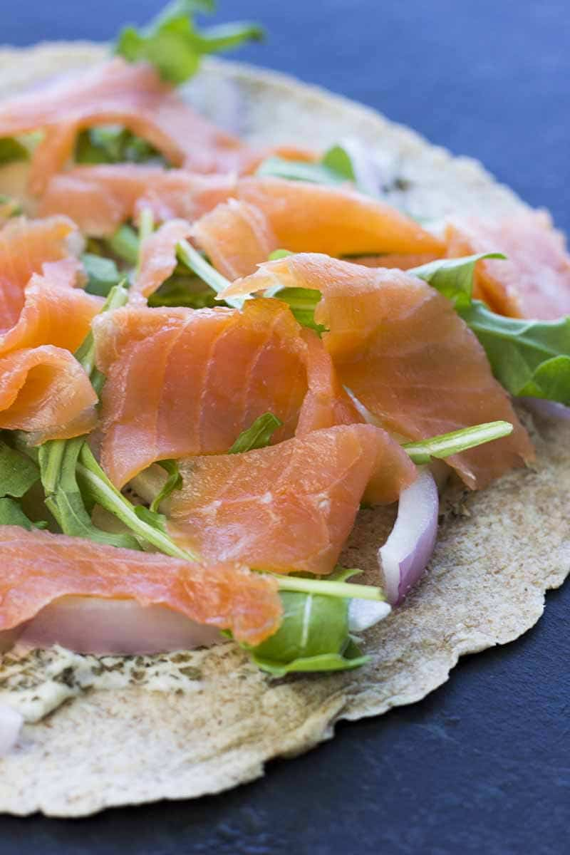 Tortilla with cream cheese, salmon, arugula, and onion on top
