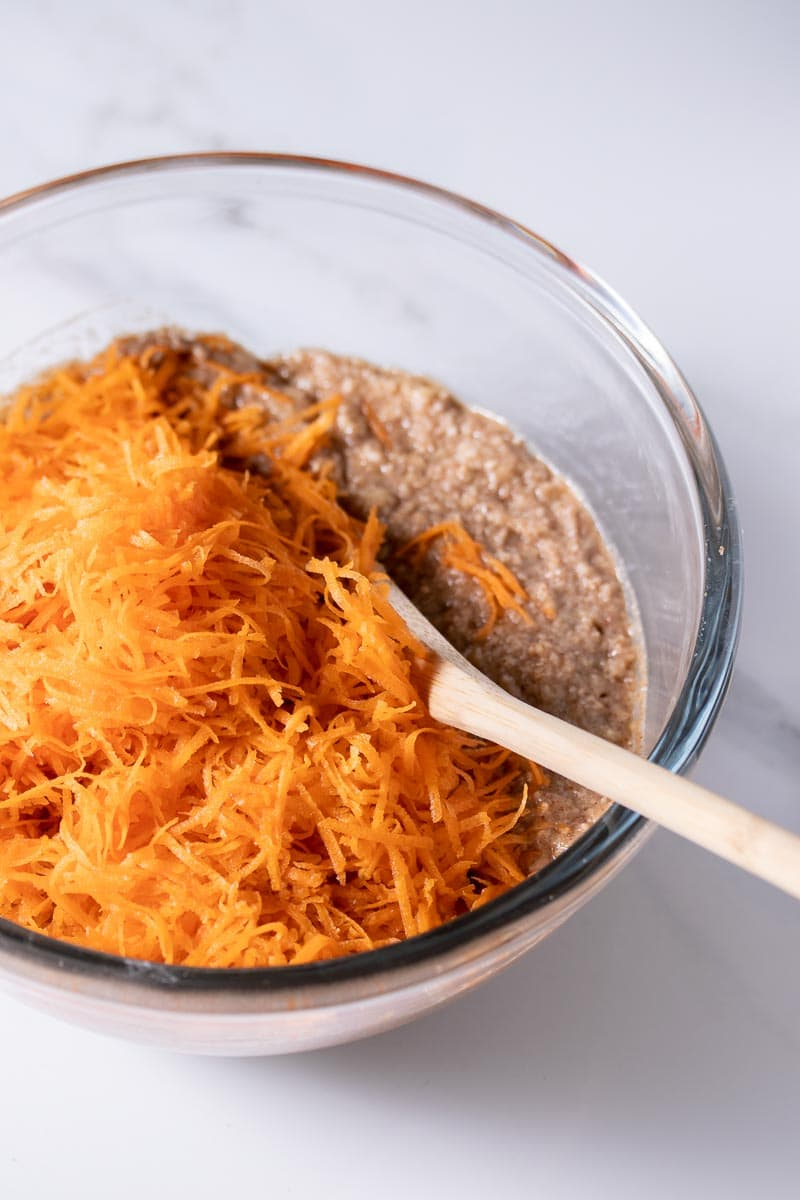Shredded carrots being added to the muffin batter