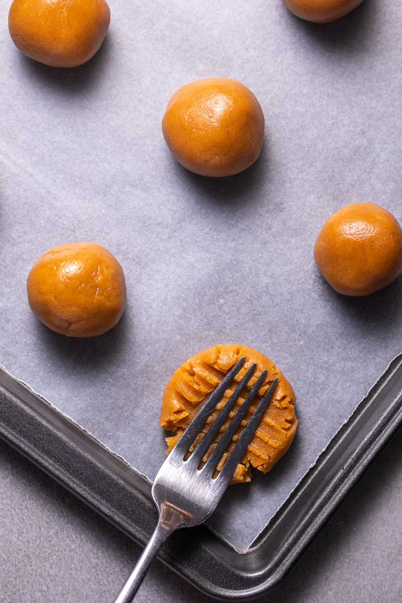 Cookie dough rolled into balls on a baking sheet with a fork flattening one