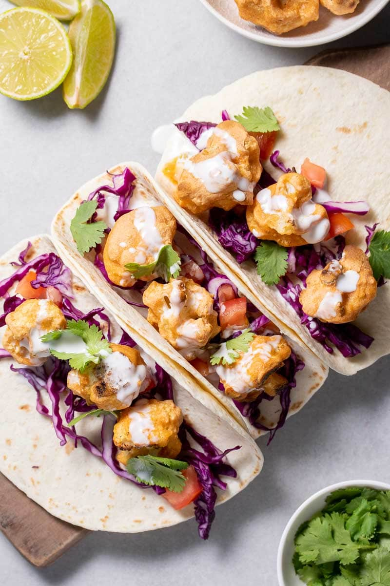 3 Low-Carb Buffalo Cauliflower Tacos on a wooden board