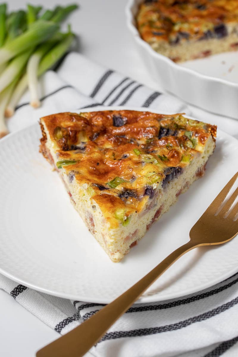 A slice of quiche served on a plate with a fork as seen from the side