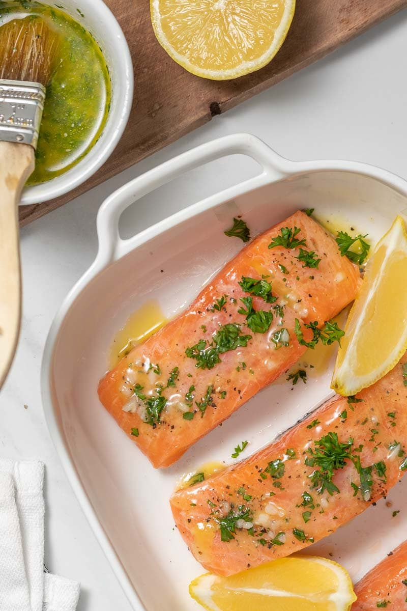 Raw salmon steaks brushed with butter, lemon, and garlic