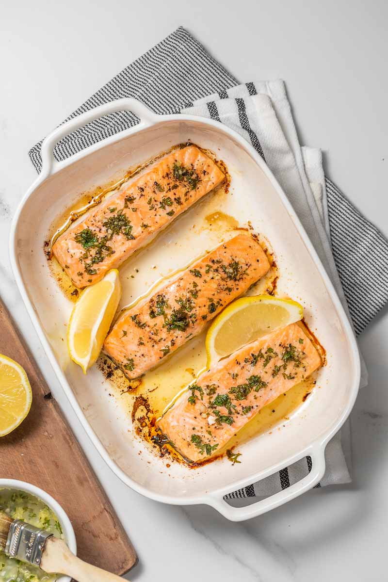 Finished salmon fillets in the baking tray with lemon wedges