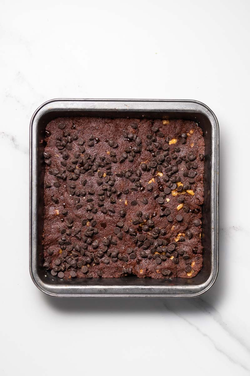 Brownie dough pressed into square baking dish with chocolate chips