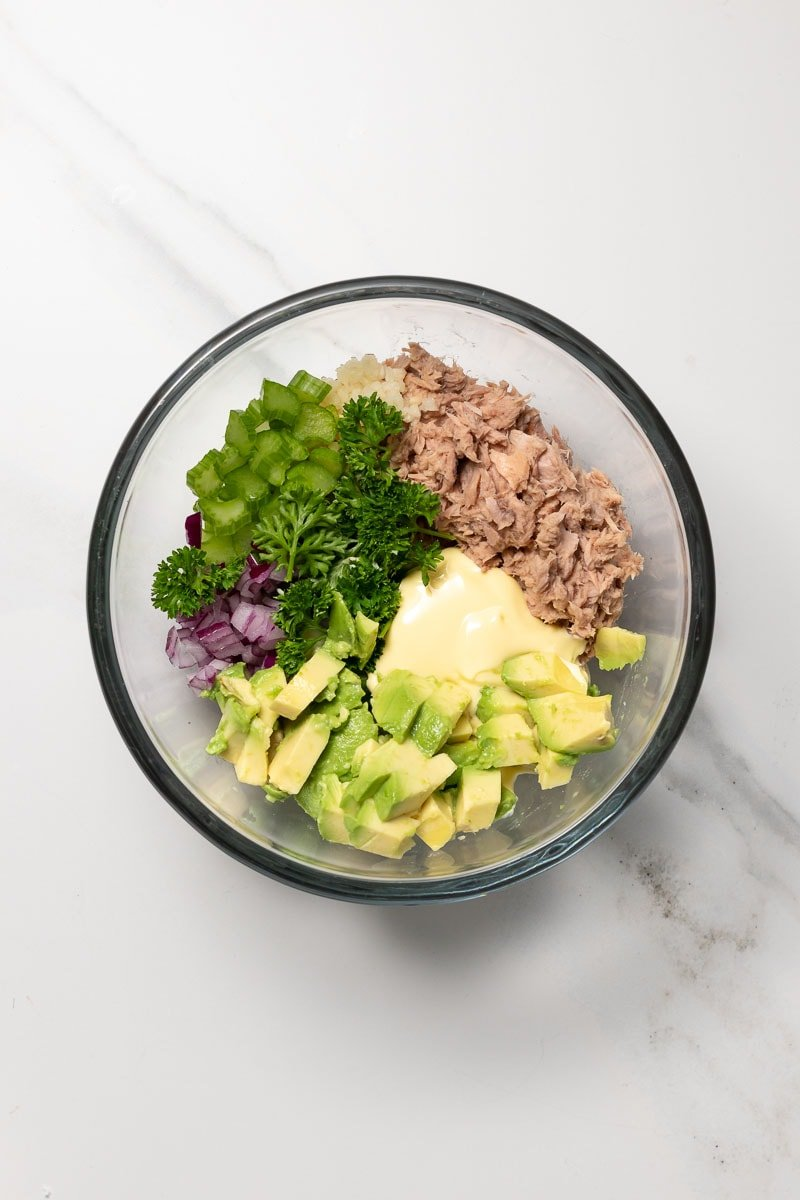 Tuna salad ingredients in a bowl before being mixed