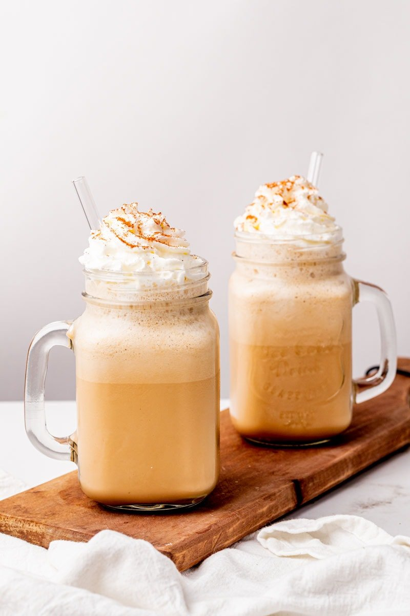 Low-carb milkshakes in two glass jars with straws, topped with whipped cream and cinnamon
