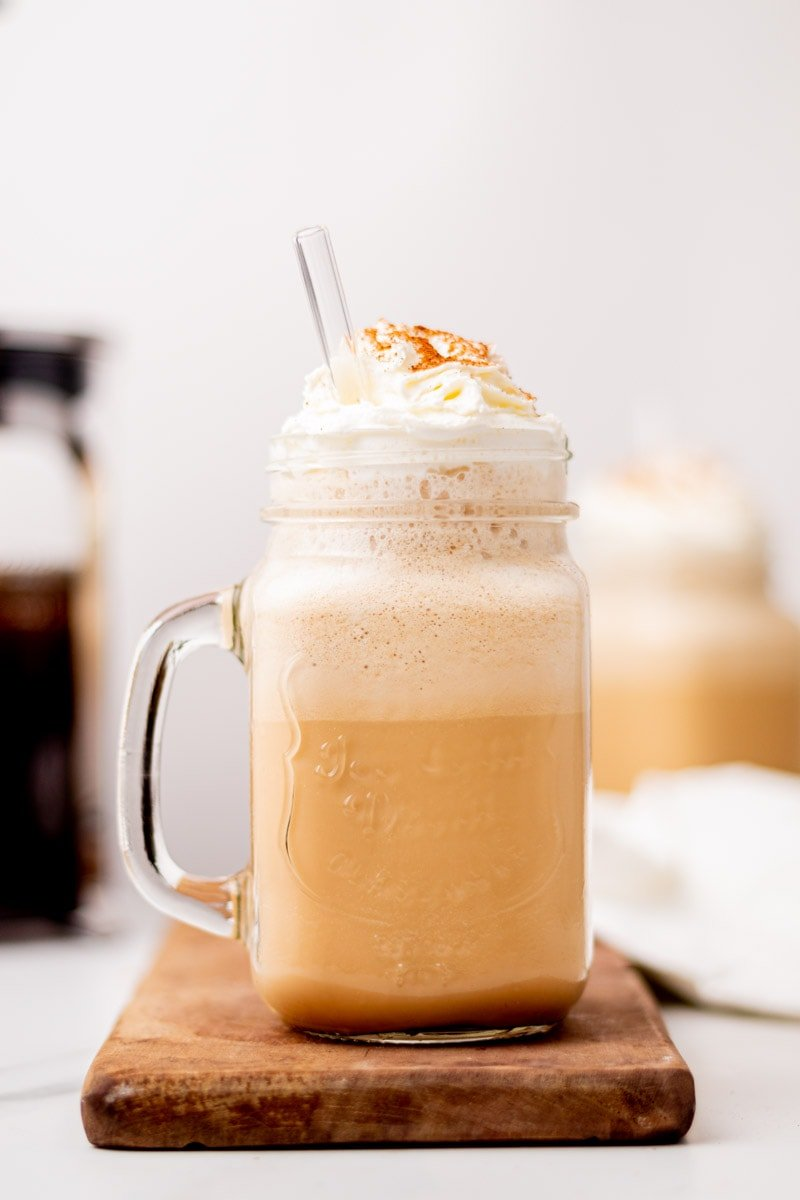 Close-up of a milkshake in a glass jar topped with whipped cream and cinnamon