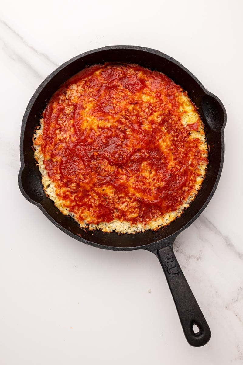 Pizza marinara sauce spread over the cauliflower base