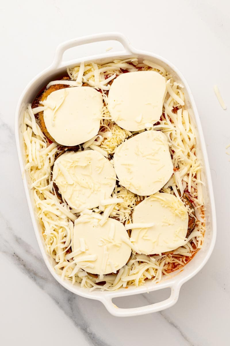 Assembled dish in a baking tray topped with parmesan and mozzarella slices