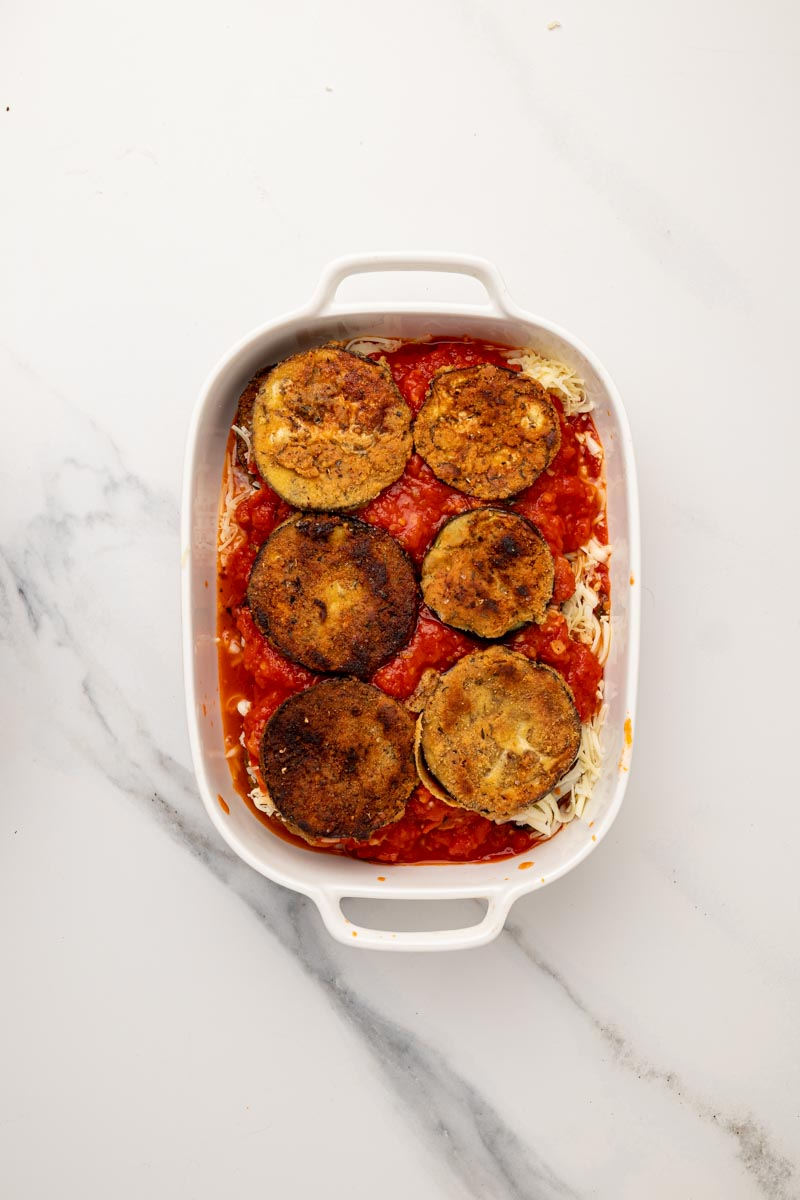 Layers of the eggplant, cheese and marinara sauce in a baking dish