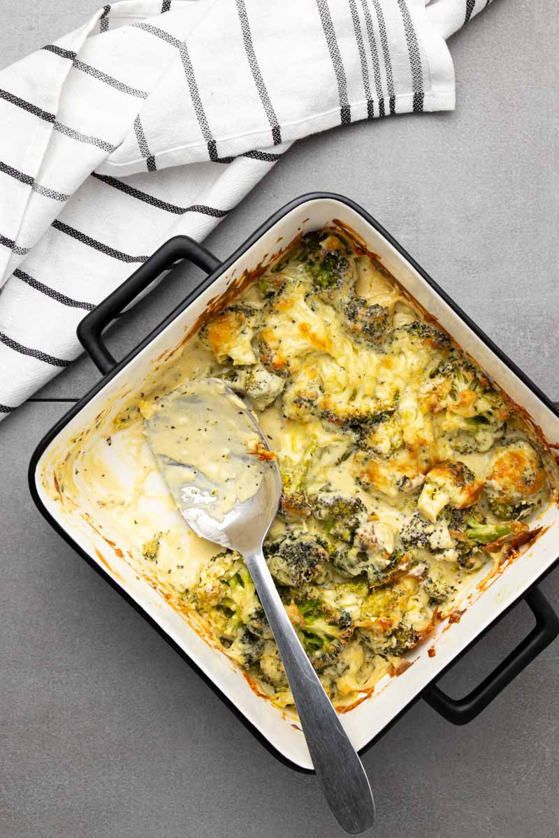 Broccoli casserole with a serving spoon and white cloth