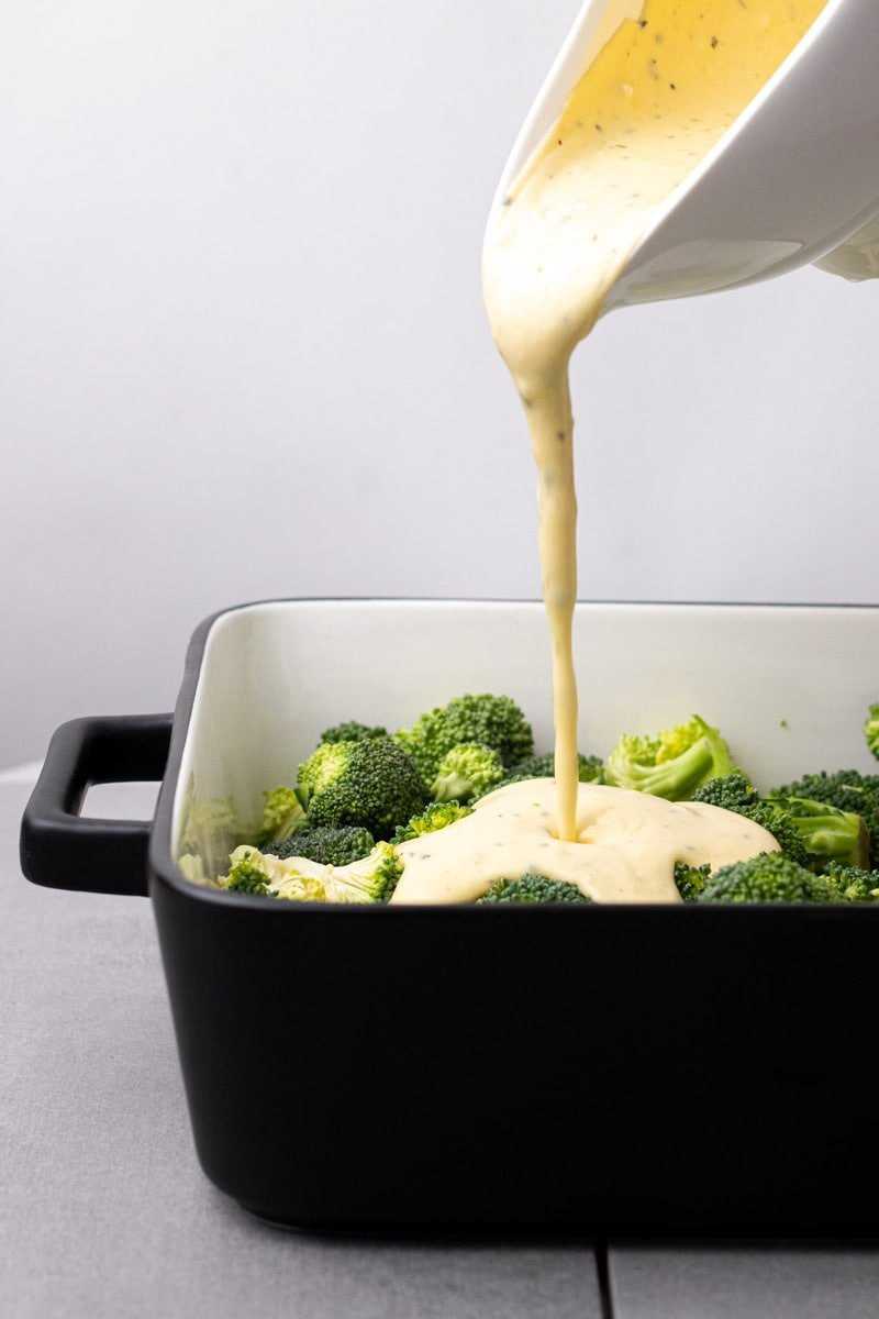 Pouring the cheese sauce over the broccoli florets