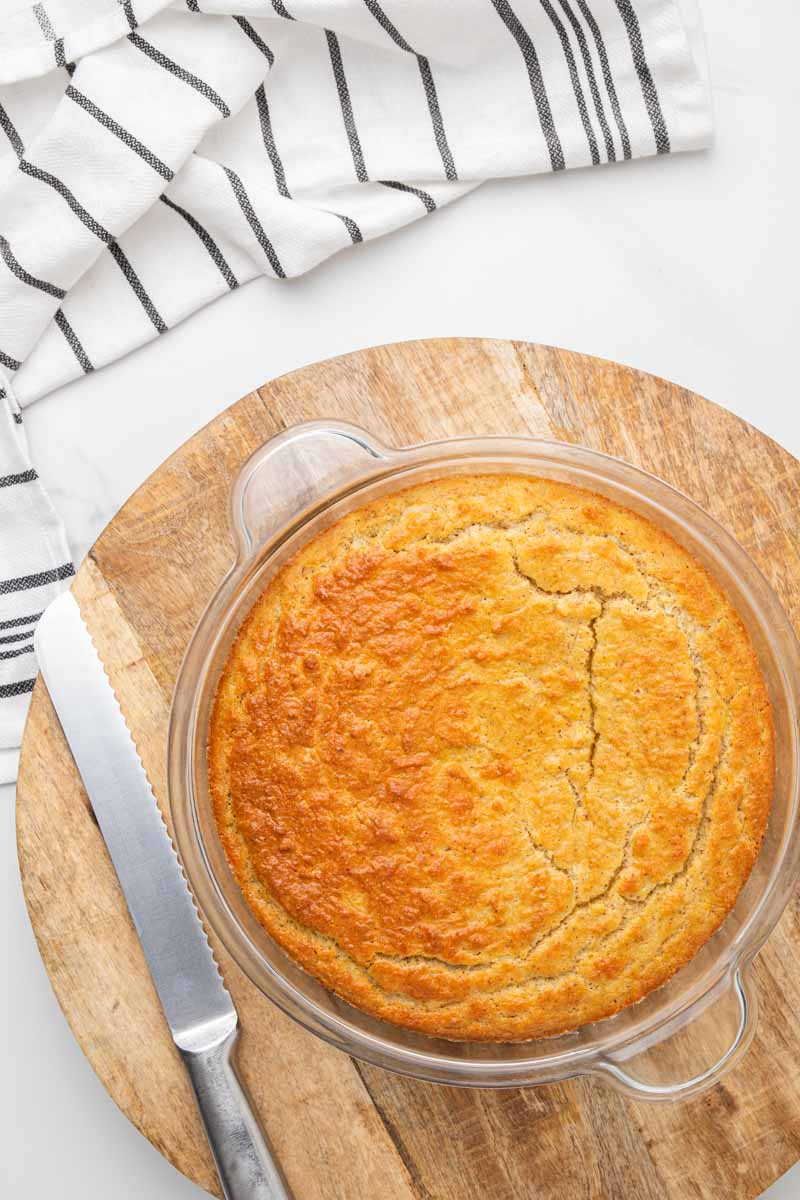 Golden brown baked cornbread with a bread knife ready to serve