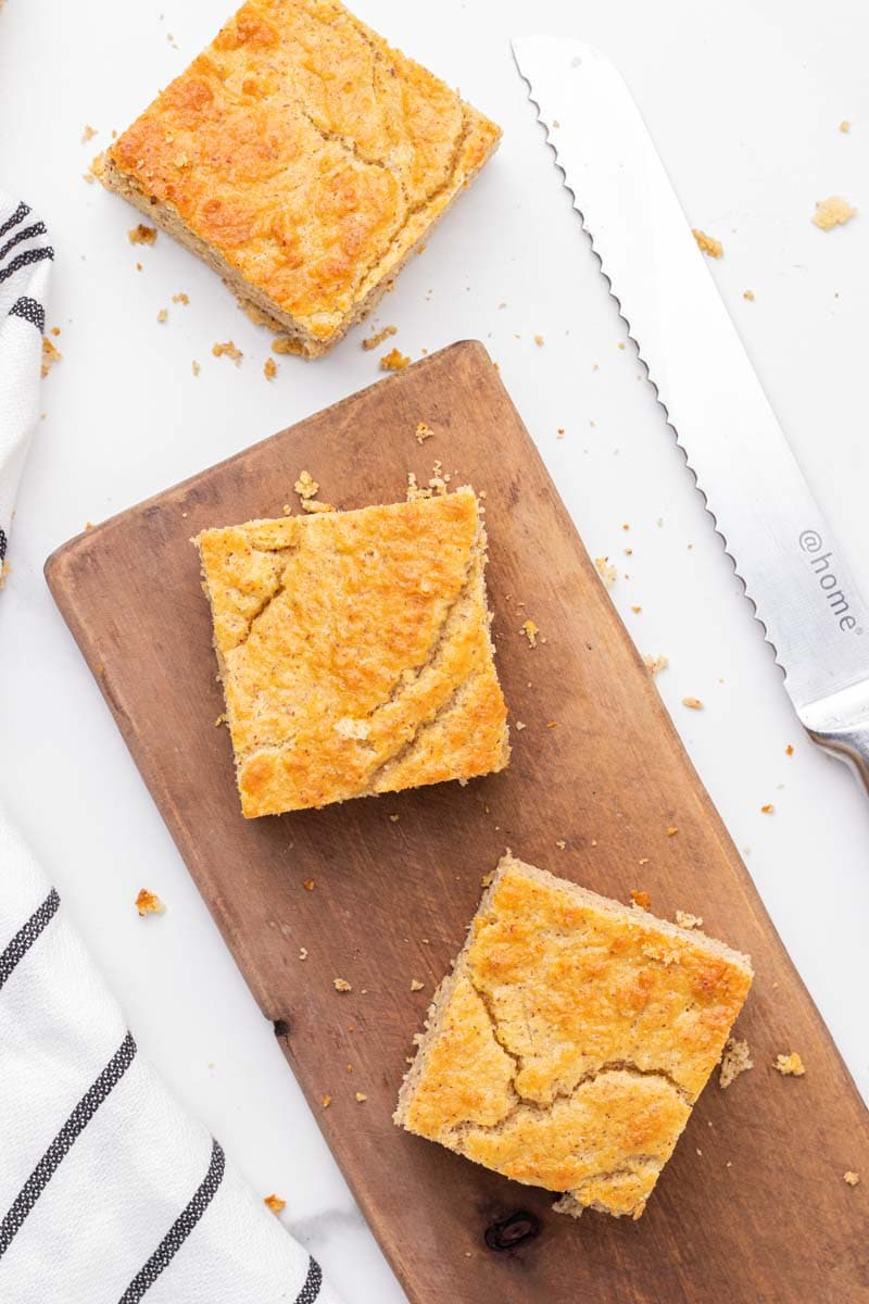 3 squares of low carb cornbread on a wooden cutting board
