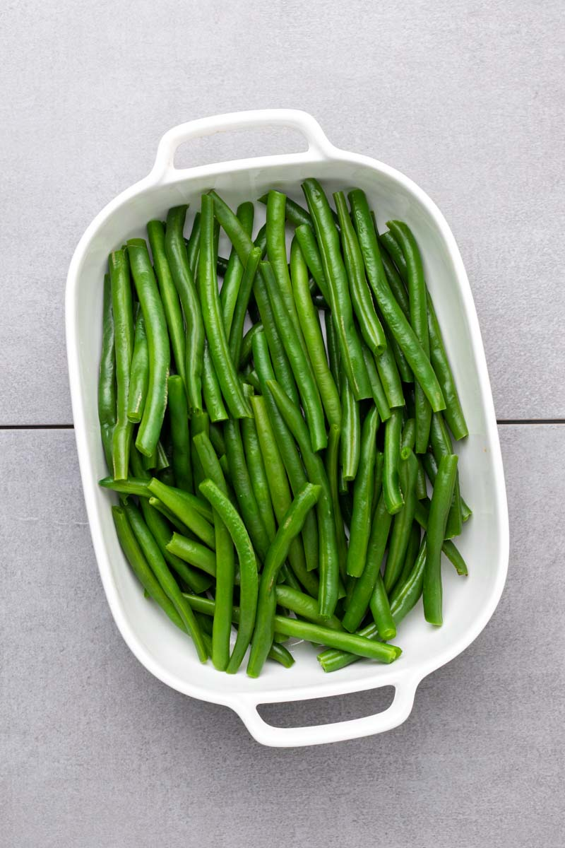 Cooked and trimmed green beans in a casserole dish