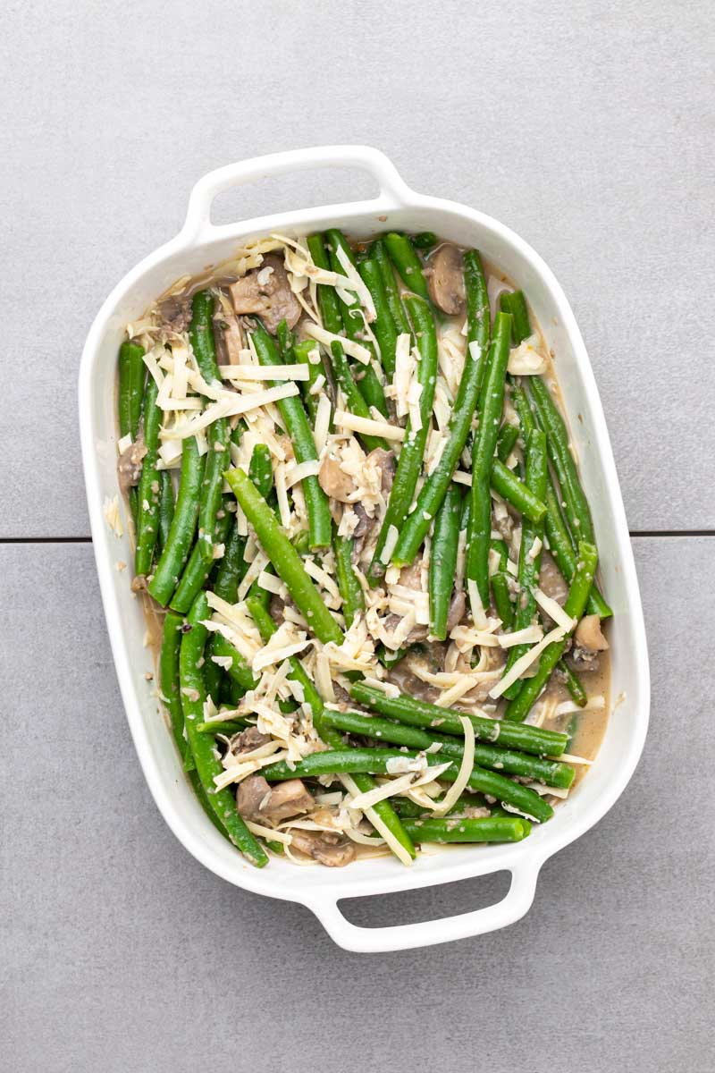 Green beans mixed with mushroom soup and cheddar cheese in the casserole dish
