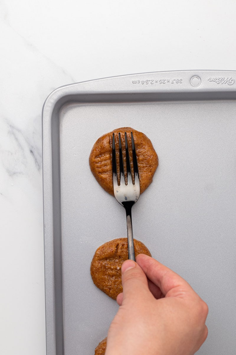 Cookies being pressed with a fork crosswise
