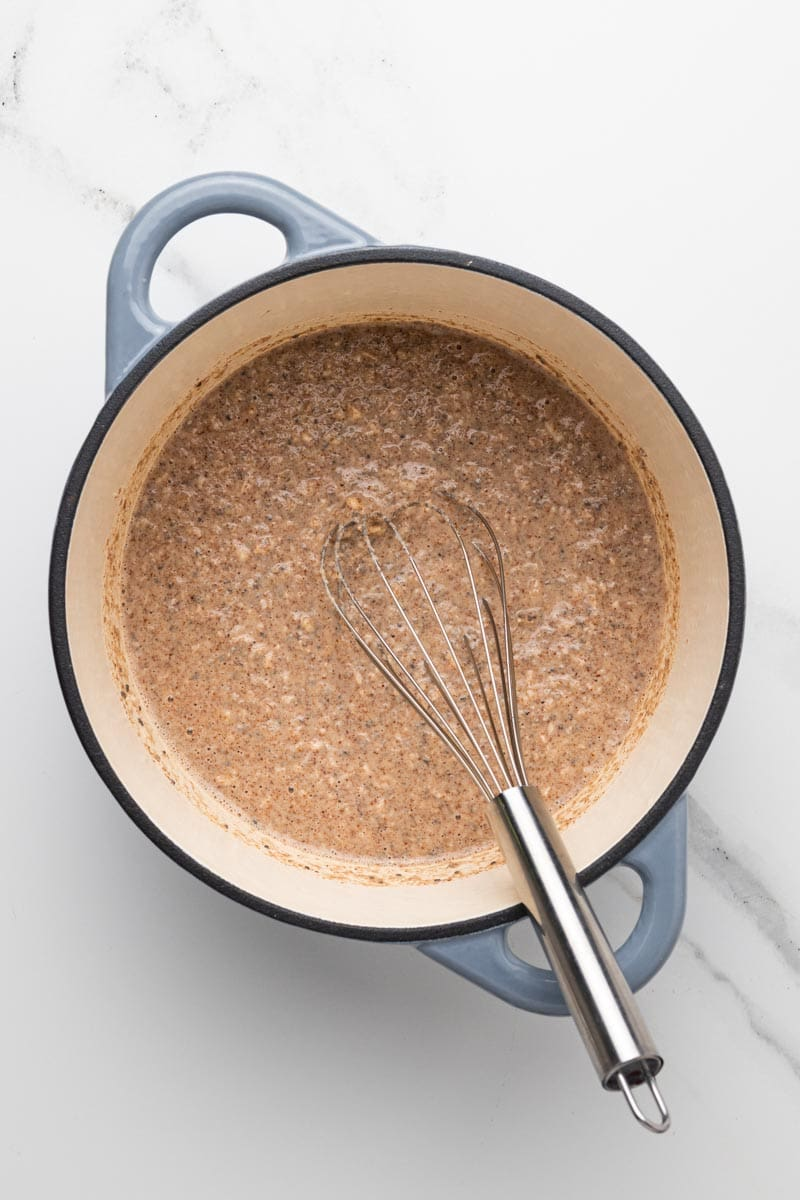 uncooked oatmeal in a cast iron dish being whisked