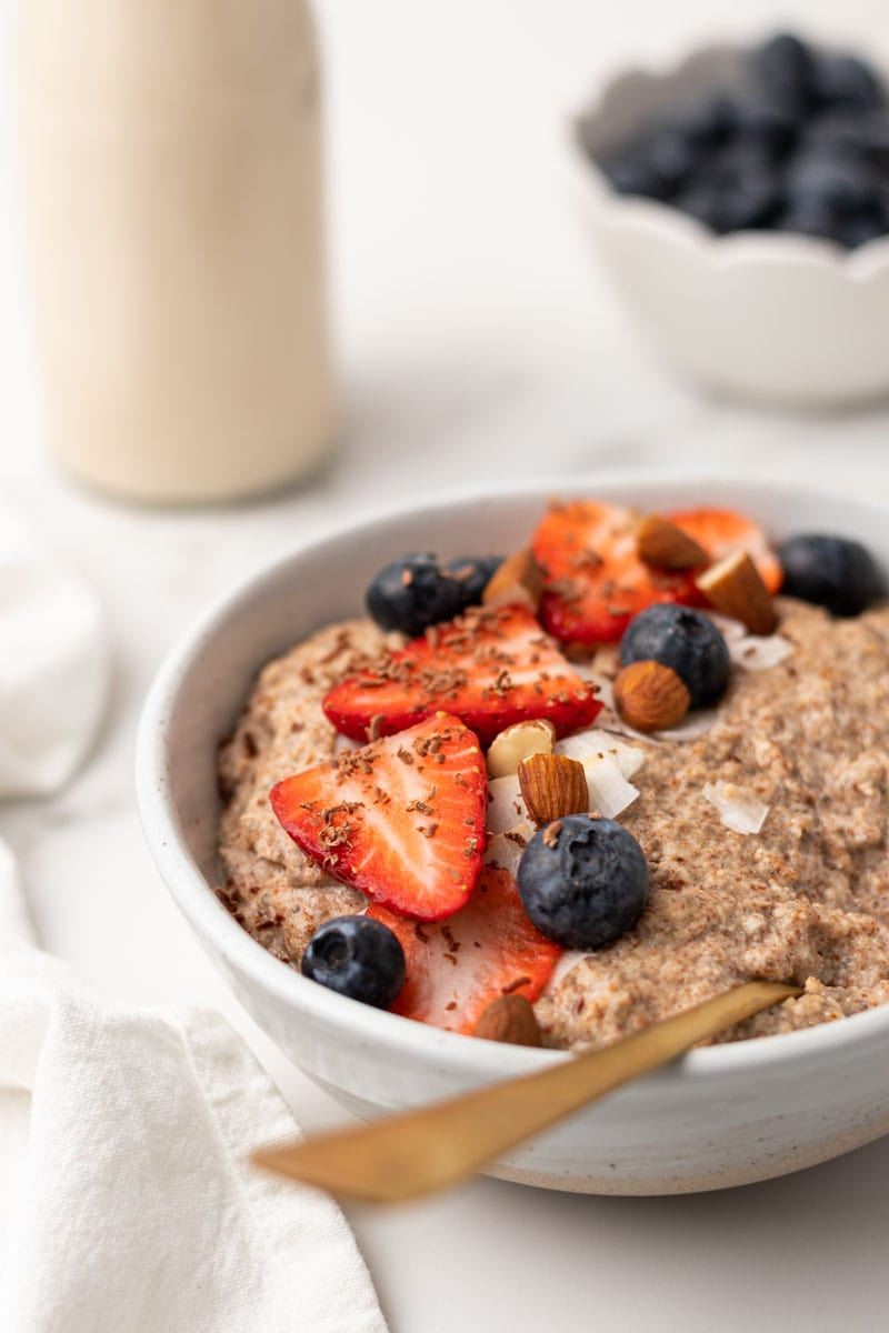 close up image of the oatmeal served with fresh fruit and nuts