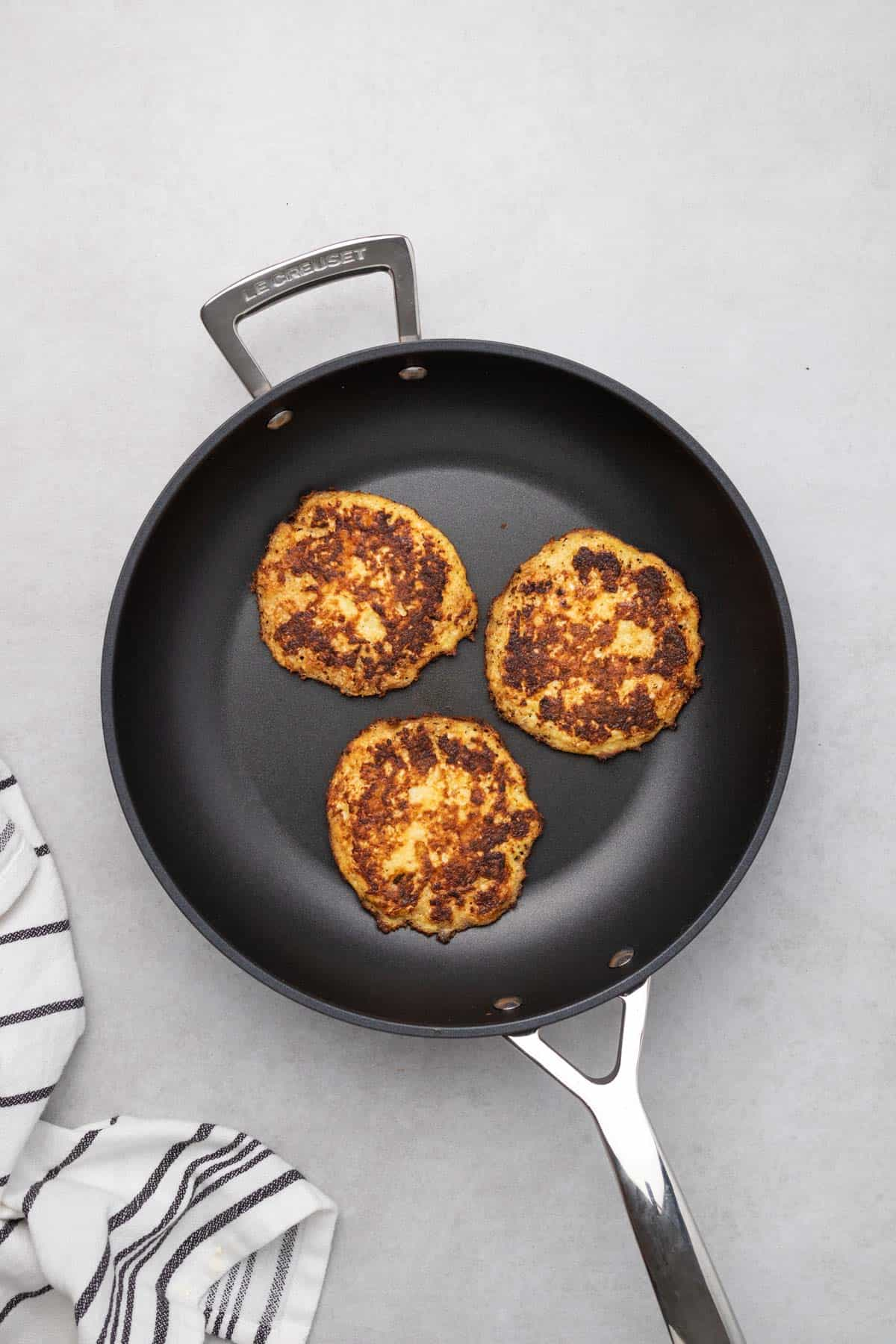 fritters frying in a black frying pan