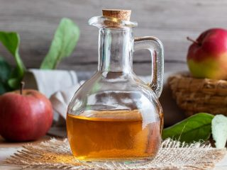Glass bottle of apple cider vinegar in front of basket with apples