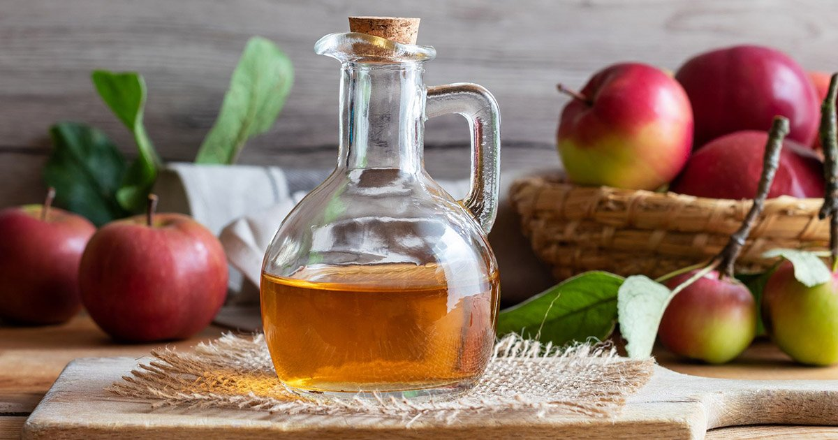Glass bottle of apple cider vinegar in front of basket with apples