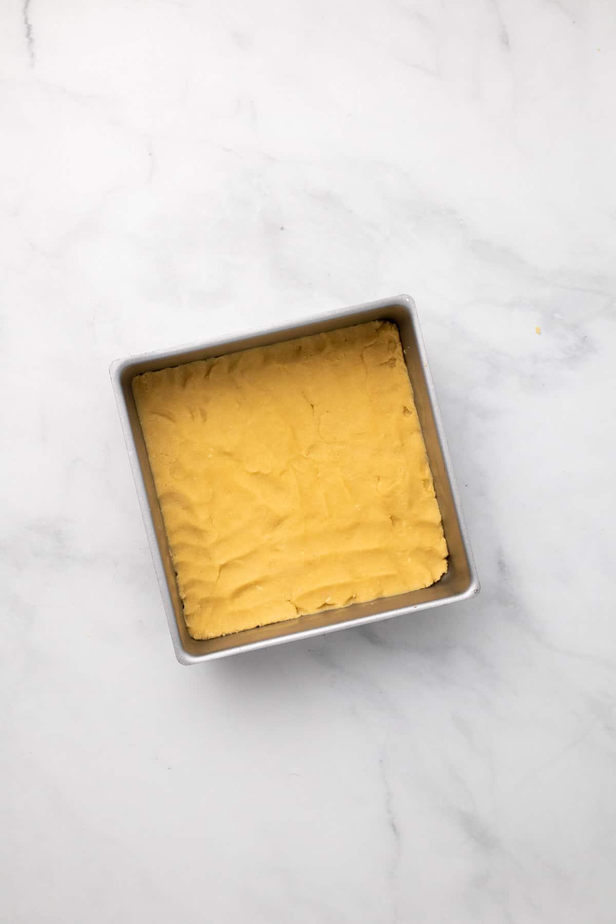 Dough pressed into a square pan