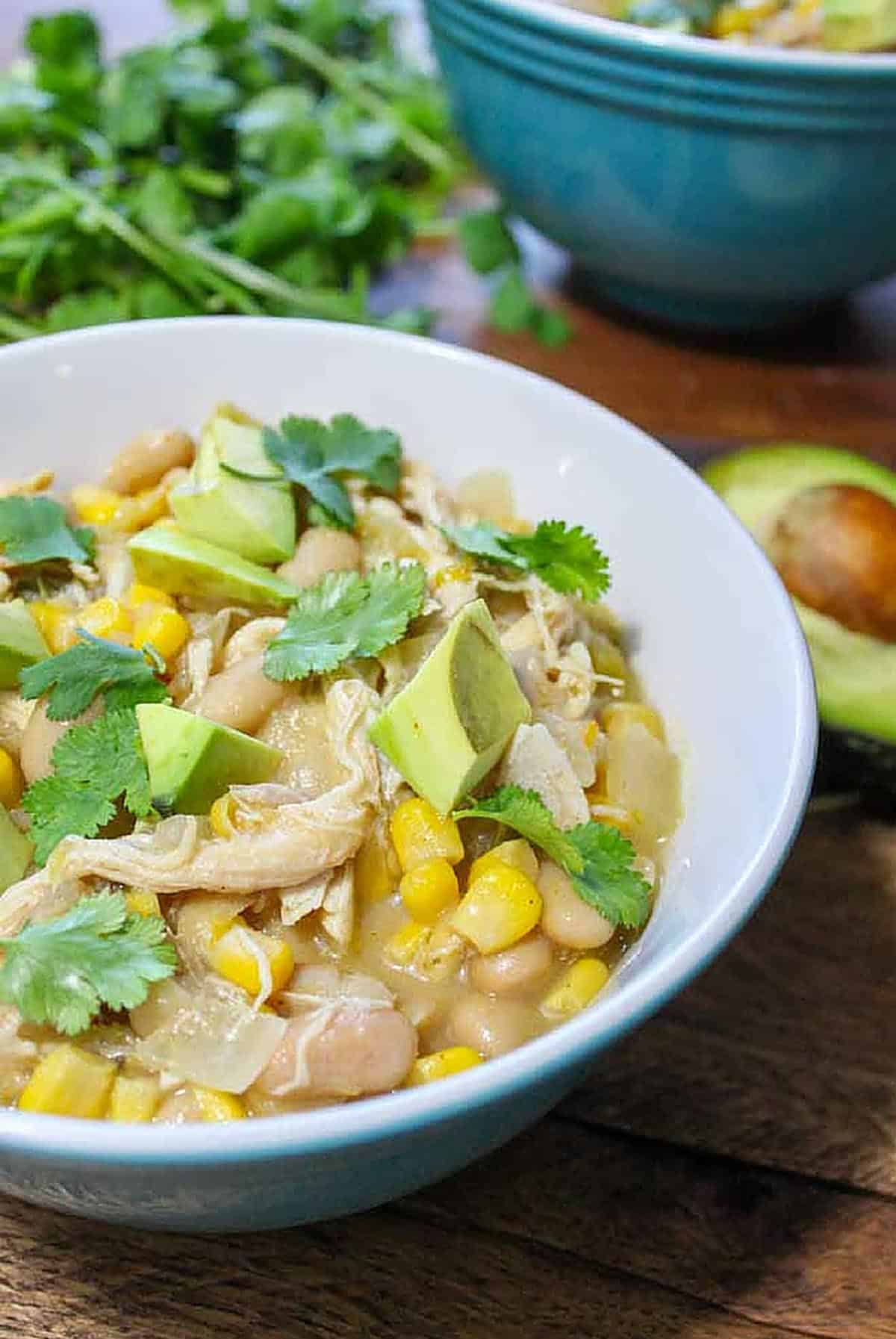 Bowl of slow cooker white chicken chili with chopped avocado and cilantro on top