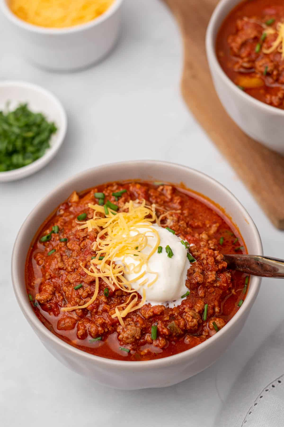 Beanless chili in a white bowl topped with sour cream, shredded cheese, and green onion
