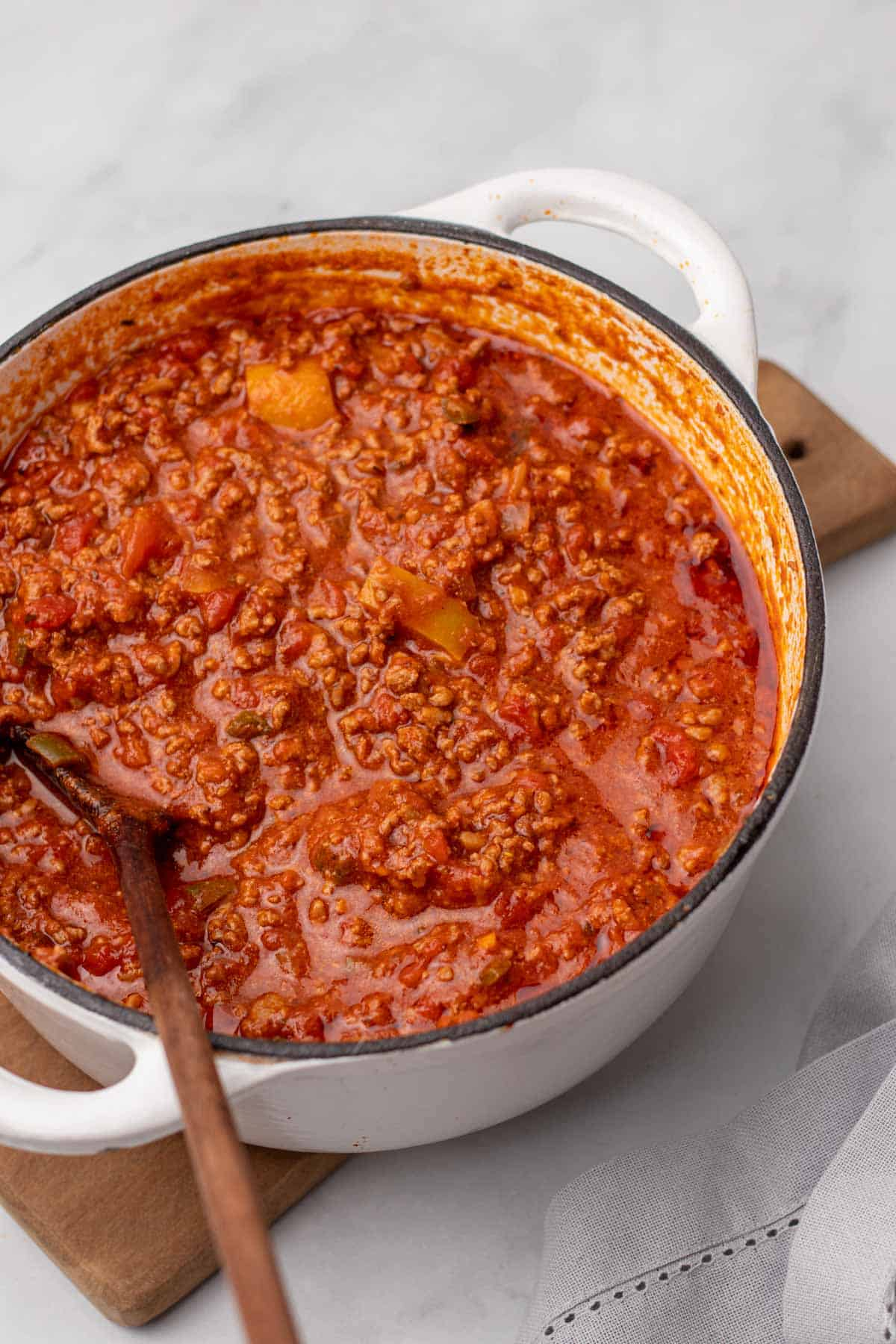Chili in a white pot with a wooden spoon
